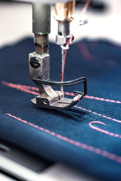 Nähmaschine stickt ein Muster in blauen Stoff - Stickerei und T-Shirt-Druck